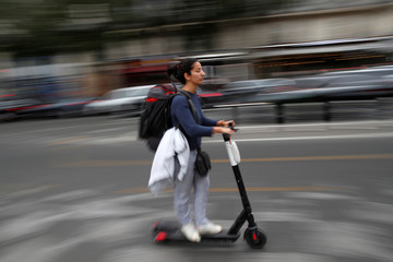 A woman rides a dock-free electric scooter in a street of Paris during a strike by all unions of the Paris transport network (RATP) against pension reform plans in Paris
