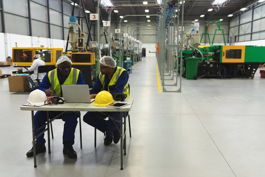Male factory workers using laptop in a factory warehouse