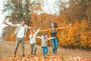 junge Familie rennt im Herbst