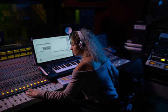 Female music producer working at the mixing desk in a sound studio