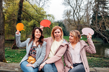 group of girls in the park doing weird expressions while holding a thought bubble on their hands. Friendship and communication concept.