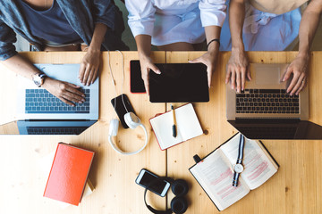 Flat lay picture of three women working with laptops and books sitting at the table together - business woman, co-working and college girls concept