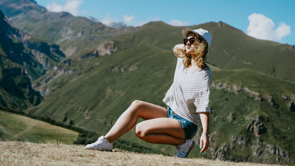 The girl in a cap and shorts in the mountains sits on the grass. Hike in the mountains, resting on a meadow, outdoor