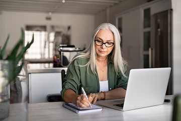 Senior fashionable woman working at home