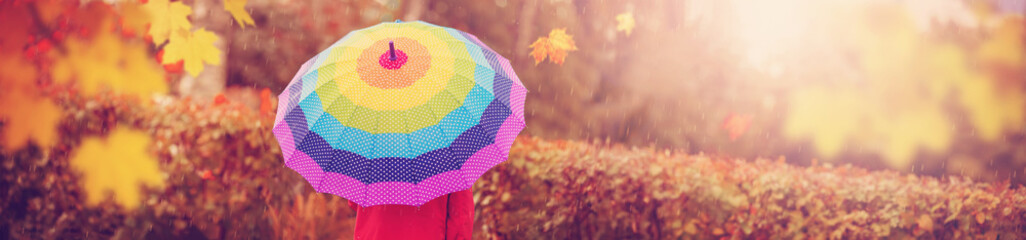 Boy holding colourful umbrella under rain in autumn