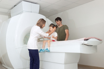 The child sits on a drawer of an MRI machine. Nearby A father and a female doctor are preparing a little girl for magnetic resonance imaging in a hospital. Nurse putting headphones on baby