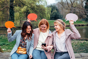 group of surprised women in the park looking at a mobile phone while holding a thought bubble on their hands. Friendship and communication concept.