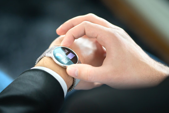 Smart watch with touch screen. Business man using wearable device with mobile technology. Smartwatch with finance report or banking app. Person wearing digital gadget in hand. Hybrid wearables concept