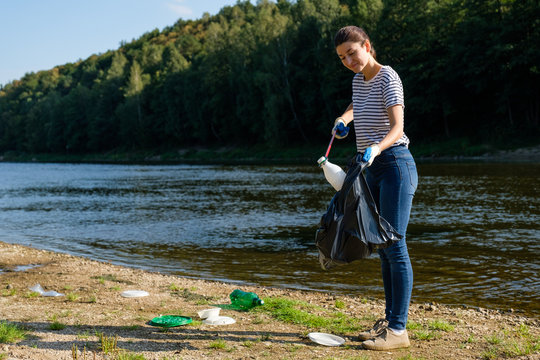 Volunteer woman picking up plastic garbage on the beach. Cleaning environment concept