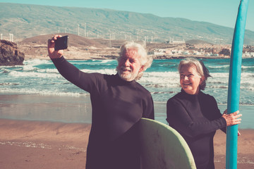 happy couple of seniors at the beach trying to go surf and having fun together - mature woman and man married taking a selfie with the wetsuits and surftables with sea or ocean at the background