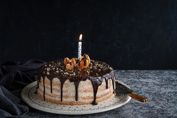 Beautifully styled and decorated birthday cake with one candle lit up, on a table, oranges, walnut and chocolate decoration, dark, moody background with negative space for title and textured tabletop