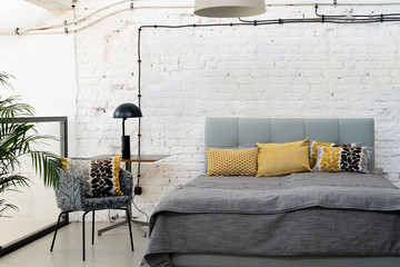 Loft apartment with white bricky wall with copy space and double bed with pillows. Interior in...