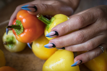 Females hands with manicured nails holds fresh organic paprika