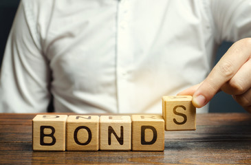 Businessman puts wooden blocks with the word Bonds. A bond is a security that indicates that the...