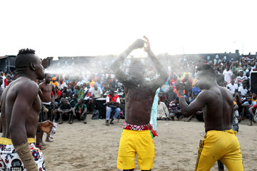A Dambe warrior splashes water on his teammates before a fight at the arena in Lagos