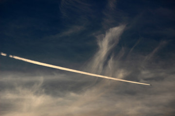 Contrails from an airplane descending through clouds in the sky