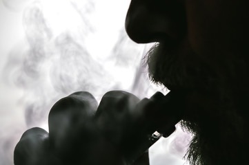 Fotobehang - Man with concealed identity smoking a controversial vape is a health risk