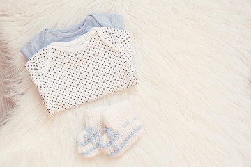 Baby Bodysuit Mockup. Styled Stock Photography. Clothes For A Boy. Jumpsuits, Rompers On A White Fur Carpet. Newborn Baby Concept. Baby Boy Clothes Set