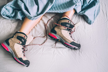 Fotobehang - All time ready for trekking. Hiker female sleeping in comfort trekking boots. Footwear on the bed sheet background concept image.