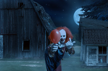 eerie clown with a balloon in hand in front of a scary scene