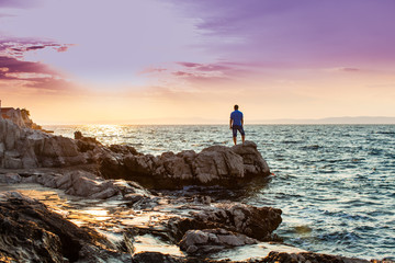 Yung man standing on a rock and looking at the sea sunset