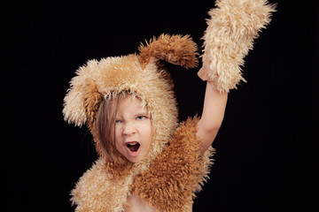 foto de estudio de una niña de 5 años con un disfraz de peluche. Fondo negro