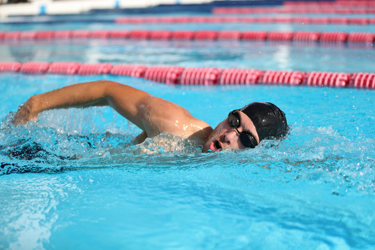 Swim competition swimmer athlete doing crawl stroke in swimming pool. Sports man male swimmer with goggles and cap breathing racing in indoor stadium. Speed exercise workout.