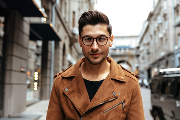 City style. Fashion. Man portrait. Handsome young man in casual clothes and glasses is looking at camera while walking in the city Wall mural