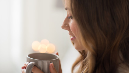 Fototapete - drink, christmas and hygge concept - close up of happy woman with lights over cup of coffee or tea at home