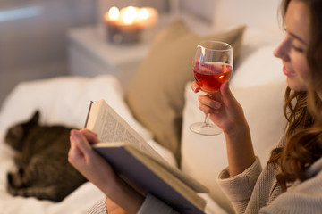 Fototapete - christmas, leisure and comfort concept - happy young woman reading book and drinking rose wine in bed at home bedroom