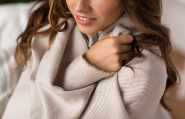 Fototapete - comfort, winter season and hygge concept - close up of young woman wrapped in warm blanket at home
