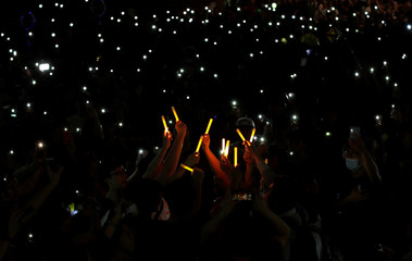 People hold up glowing sticks and mobile phones during the Mid-Autumn Festival, in Sha Tin, Hong Kong
