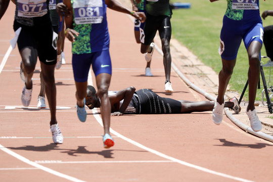 A competitor looks at runners after falling on the finish line during the men's 800 meters run at Kenya's world championship trials at the Nyayo national stadium Nairobi