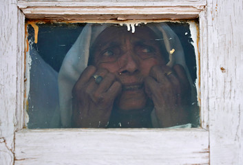 A Kashmiri woman reacts as she looks out from a window of a mosque at a protest site after Friday prayers during restrictions, in Srinagar