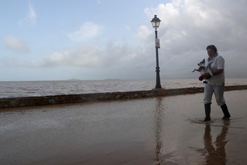 A woman holds her dog as she walks along the beach after heavy rains in Los Alcazares