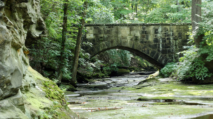 old stone bridge over a river with lush green landscape and large boulder rocks