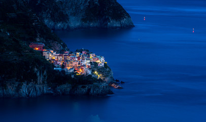Fotobehang Liguria The fishing village of Manarola in Cinque Terre, Italy, illuminated at dusk during blue hour with the Mediterranean sea as background
