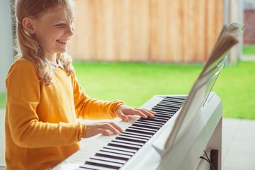 Portrait of pretty little girl having piano lesson at modern white e-piano