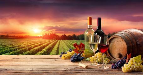 Fototapeta Barrel Wineglasses And Bottle In Vineyard At Sunset