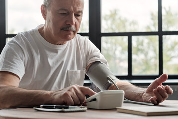 Old hispanic man feeling bad using a home blood pressure machine to check his health in the morning
