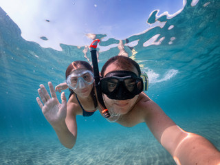 Young couple taking a selfie underwater during snorkeling.