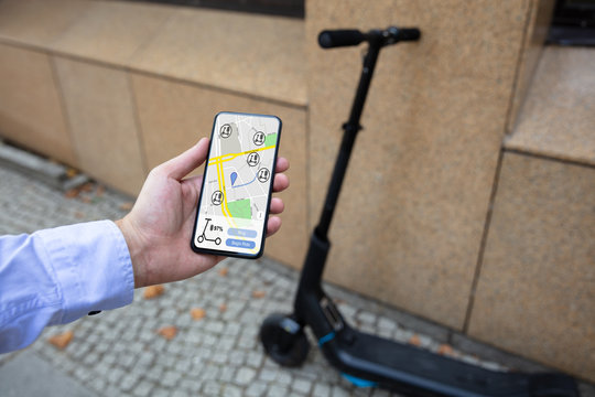 Young Man Using Electric Scooter Ride Sharing App