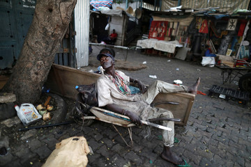 A man whose job is to carry people's heavy shoppings in his wheelbarrow to their homes waits for customers in Dakar