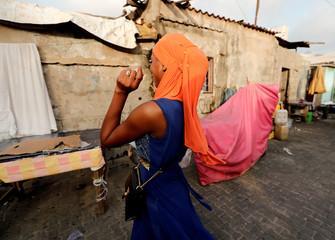 A woman reacts as she walks in Dakar