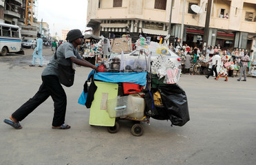 A street vendor pushes a cart loaded with goods for sale in Dakar