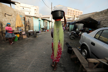 A girl who is a street vendor carries a basin filled with water in sachets in Dakar
