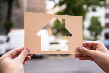 Hands Holding Paper With Cutout House
