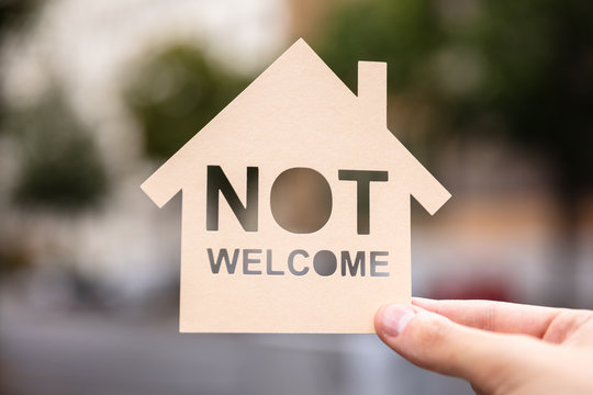 Hands Holding Paper With Cutout House And Non Welcome Words