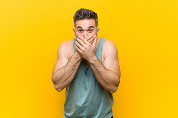 Young fitness man against a yellow background shocked covering mouth with hands.