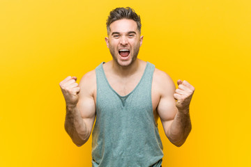 Young fitness man against a yellow background cheering carefree and excited. Victory concept.